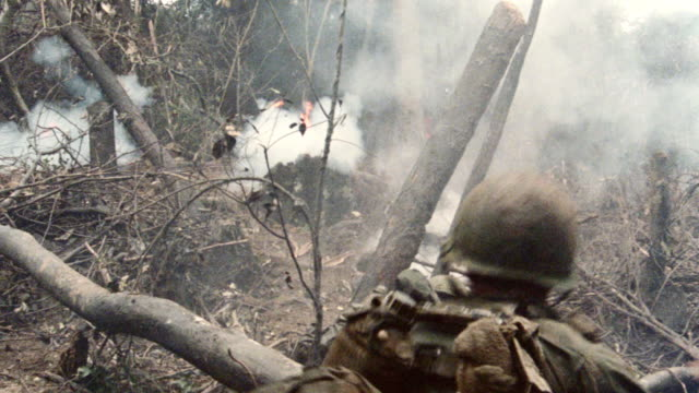a soldier throws a grenade into a smokey jungle. - vietnam war stock videos & royalty-free footage