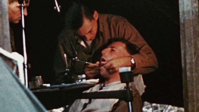 S soldier undergoing dental procedure at field hospital in Okinawa Japan during WWII