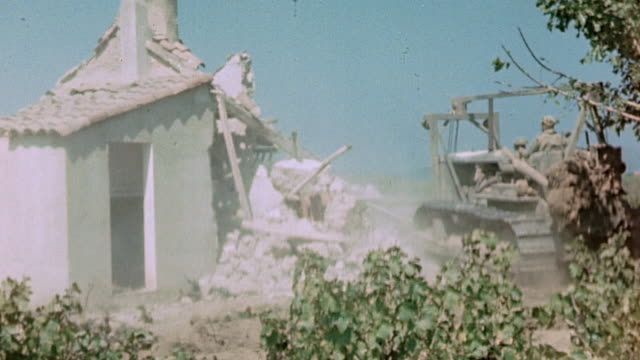 Soldier using bulldozer to knock down small Mediterranean cottage / Ramatuelle France