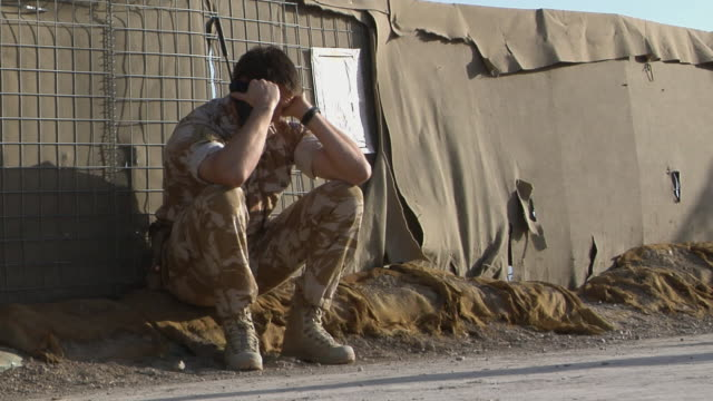 soldier using walkie-talkie, rubbing eyes / musa qala, helmand province, afghanistan. - britisches militär stock-videos und b-roll-filmmaterial