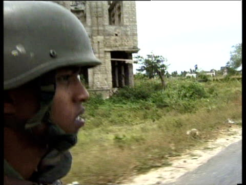 soldier views bomb damaged buildings of jaffna from back of moving truck sri lanka; 1998 - sri lanka stock-videos und b-roll-filmmaterial