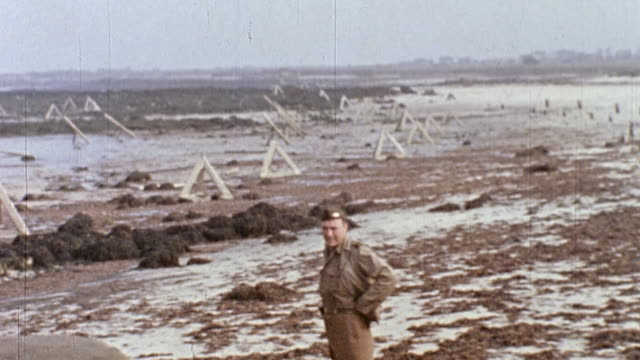 soldier walking along the beach, past the ruins of barbed wire barricades / normandy, france - 1944 stock videos & royalty-free footage