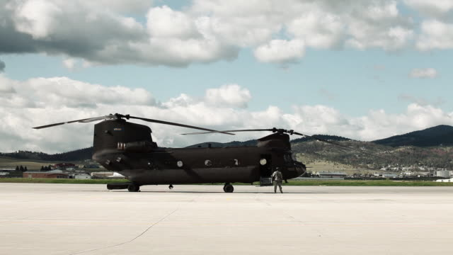 Soldier walking away from a CH-47 Chinook Helicopter as it powers up.