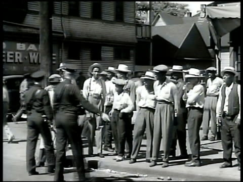 SOLDIERS Soldier walking in city POLICE Two Caucasian policemen dispersing small crowd of AfricanAmericans on corner Firemen putting out flaming car...