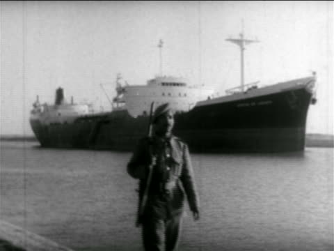 b/w 1956 soldier walking on shore with freighter in suez canal in background / suez crisis / newsreel - suez canal stock videos and b-roll footage