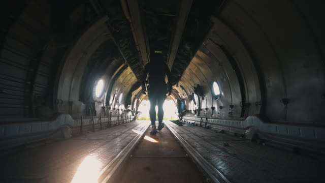 vídeos de stock e filmes b-roll de soldier walking through an abandoned military plane - tropa
