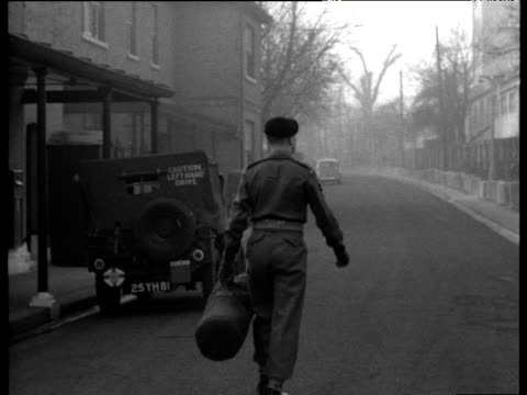 soldier walks up street carrying kit bag turns and waves leaving national service; 1956 - 1956 stock-videos und b-roll-filmmaterial