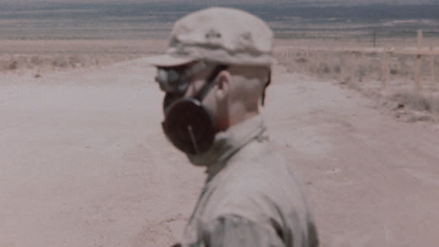 soldier wearing gas mask fitted with dark lenses for nuclear testing both on and off and turning head to demonstrate / new mexico united states - white sands missile range stock videos & royalty-free footage