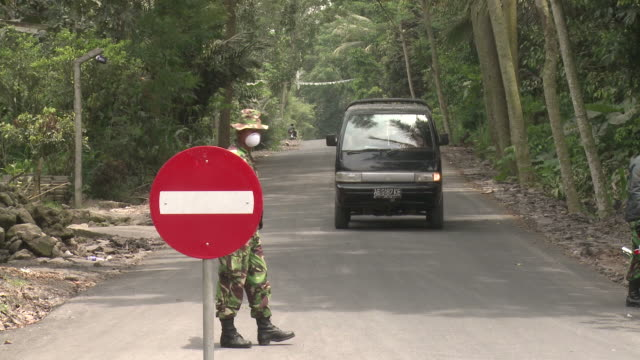 Soldier wearing mask mans checkpoint after Merapi eruption, Indonesia 28 October 2010 / AUDIO