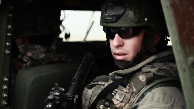 vidéos et rushes de soldier wearing sunglasses looking out side door of humvee.  - armée américaine