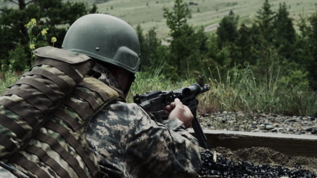 Soldier with a belt-fed machine gun. He pulls back on a lever on the firearm and pushes it back.
