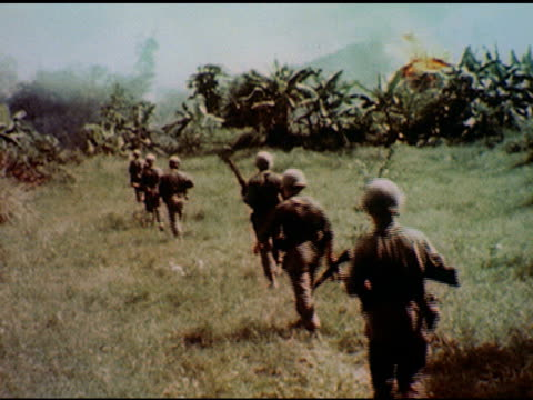 / soldier with gun approaches recently exploded structure and moves rubble / two soldiers kneel one talks on radio with cord / line of soldiers march... - vietnamkrieg stock-videos und b-roll-filmmaterial