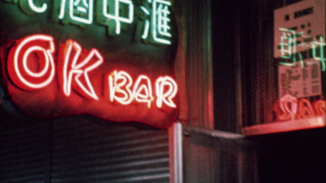 a us soldier with his arm around an asian woman exit the ok bar and walk down the sidewalk. - anno 1967 video stock e b–roll