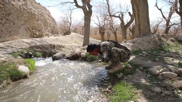 MS A soldier with the Afghan National Army washes in an irrigation ditch during a patrol on March 29 2014 near Pule Alam Afghanistan