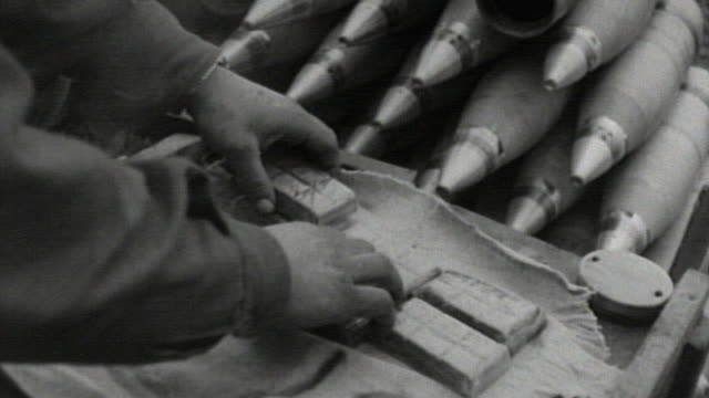 """soldier wrapping boxes of """"wound tablets"""" in burlap and tying off the ends beside stack of 105mm howitzer shell casings / france - 荒い麻布点の映像素材/bロール"""