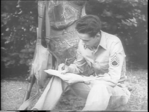 a soldier writes a letter / a woman excitedly opens a letter / in the letter the soldier saw an outdoor movie and it reminded him of home / huge... - anno 1943 video stock e b–roll