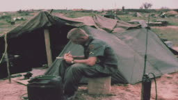 Soldier writing letter outside pup tent at camp / Saigon