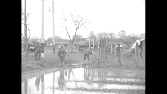 soldiers adjust barbed wire in a muddy field as a rickshaw runs past in the distance / closer shot of soldiers and barbed wire / chinese people walk... - 1910 stock videos & royalty-free footage