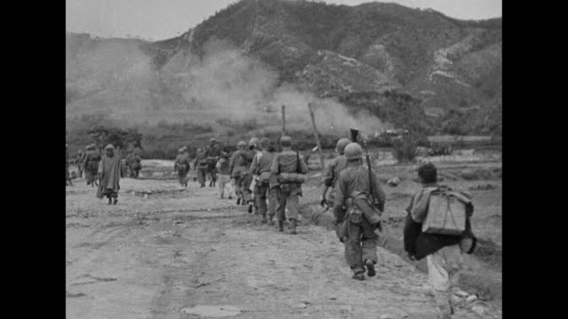 soldiers advance along road during korean war / us lt. gen. james a. van fleet rides in jeep past camera, with dog behind him / van fleet, who... - vangen stock-videos und b-roll-filmmaterial