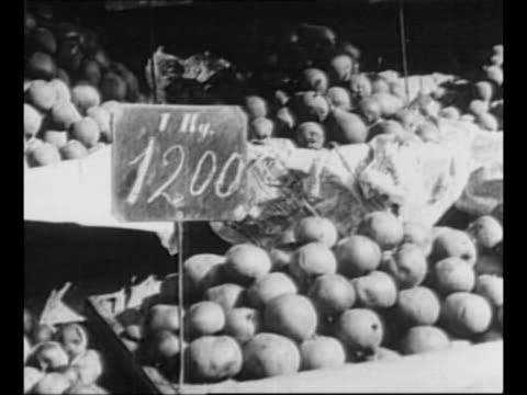 soldiers and civilians in street / montage market in vienna with bins of fruit and vegetables bearing high price tags / merchant takes money from... - インフレ点の映像素材/bロール