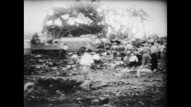 / soldiers and civilians milling about site of seven truck explosion / men walking across rubble searching for bodies / a room full of dead bodies...