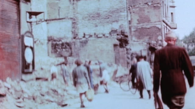 soldiers and civilians walking driving and pushing handcarts through air raid rubble - 1945 stock-videos und b-roll-filmmaterial