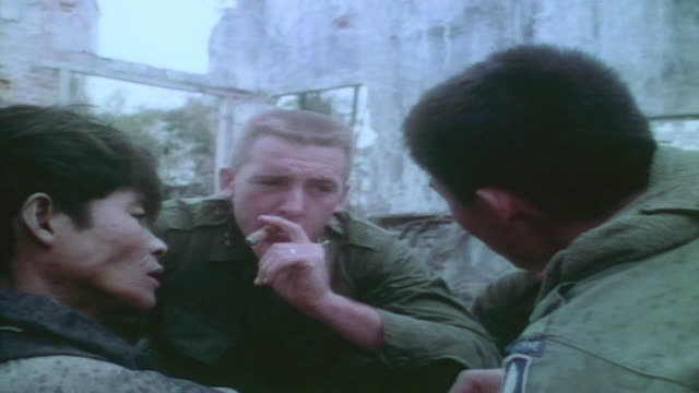 soldiers and interpreter interrogating captured viet cong prisoner / vietnam - 言語翻訳点の映像素材/bロール