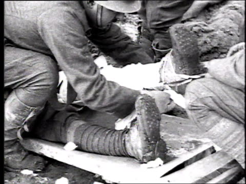 Soldiers and medics bandaging leg of wounded man on stretcher / France