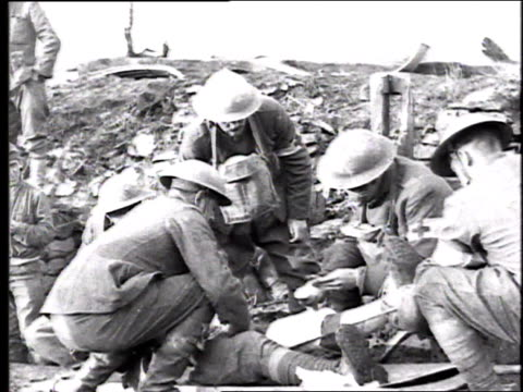soldiers and medics in field bandaging and splinting the leg of a wounded soldier / france - 1918 stock videos & royalty-free footage