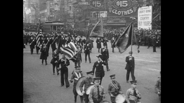 US soldiers and naval band march on street with banners / cars outfitted with banners / Boy Scouts marching