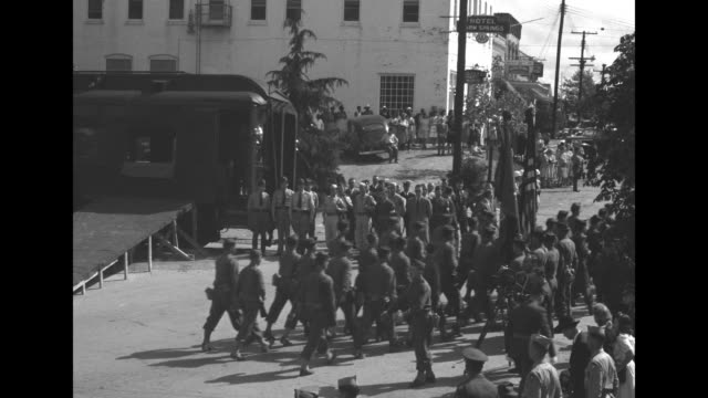 vídeos de stock e filmes b-roll de soldiers and people in street in warm springs ga / us soldiers march in foreground at the warm springs train station as crowd looks on train stands... - pólio