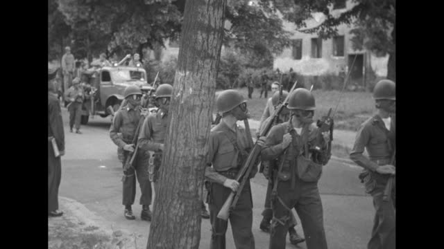 vs soldiers and police walk around streets and field in gas masks jabbing with bayonets as they prepare for third world festival of youth and... - 1951 stock-videos und b-roll-filmmaterial