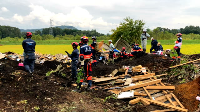 soldiers and rescue workers search through mud covering a building that was destroyed by a landslide caused by an earthquake on september 7 2018 in... - ボランティア点の映像素材/bロール