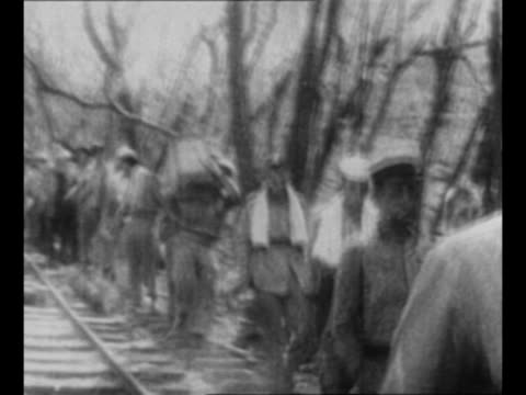 us soldiers and sailors walk now pows after surrender in battle of corregidor / japanese soldiers point bayoneted rifles at us troops with hands... - japanese surrender stock videos and b-roll footage