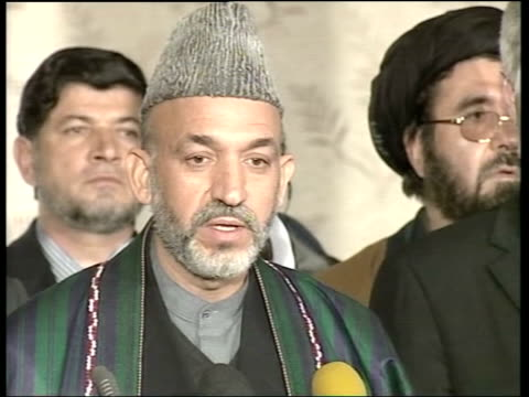 US soldiers and Taliban forces clash Kabul INT Interim Afghan Leader Hamid Karzai shaking hands with UN Secretary General Kofi Annan TILT UP LMS...