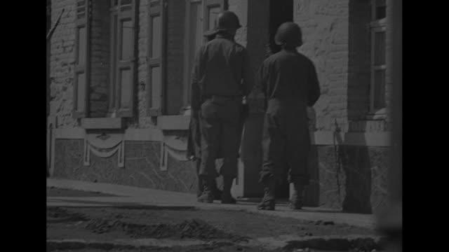 soldiers and tank in street in village / german officer talking through window in building to german soldiers inside / two us soldiers standing next... - deutsches militär stock-videos und b-roll-filmmaterial