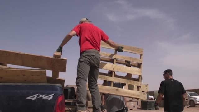 US soldiers and volunteers on Nigerien Air Base 201 Agadez Niger disassemble old pallets to reuse the wood to build desks for a local school in Agadez