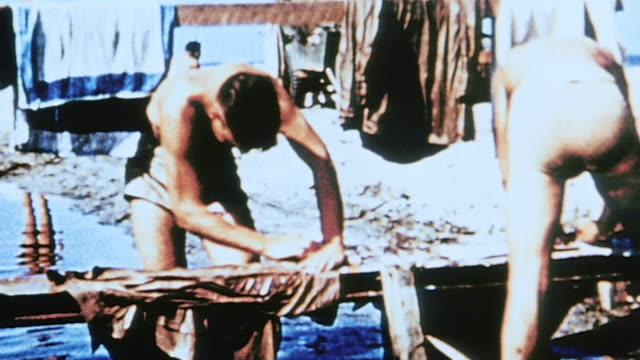 vídeos de stock, filmes e b-roll de soldiers at camp bathing doing laundry and getting a haircut and truck arriving with large group of soldiers on the back - superexposto