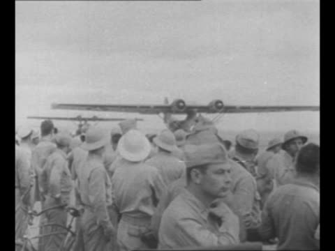 soldiers at south pacific base stand on field as pby bomber approaches, taxiing, followed by another plane / montage military personnel help capt.... - south pacific ocean stock videos & royalty-free footage