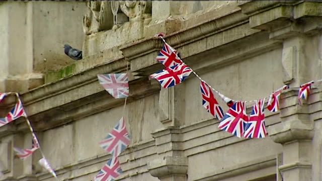 soldiers await budget cuts plans; england: wiltshire: warminster ext people and cars along quiet high street union jack bunting hanging on building... - union army stock videos & royalty-free footage