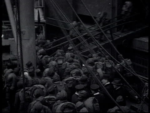 vídeos de stock e filmes b-roll de ws soldiers boarding a ship as a large group of soldiers is waiting to board all carrying packs on their backs - 1919