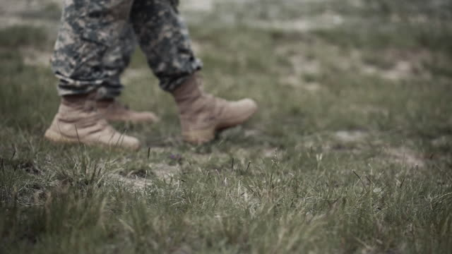vídeos de stock e filmes b-roll de soldiers' boots walking across the field - treino militar