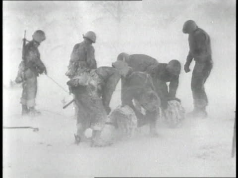 Soldiers build barbed wire fences in a blizzard during the Battle of the Bulge