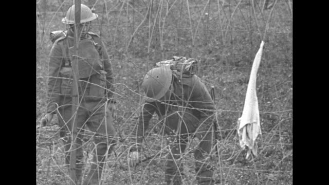 soldiers building barbed wire obstacle across field / scottish soldier playing bagpipe; soldiers working in bg; pan down his uniform with kilt / pan... - maginot linie stock-videos und b-roll-filmmaterial