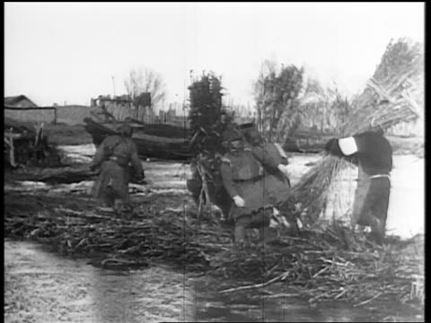 B/W 1931 soldiers building bridge with branches on water / Japan invading Manchuria