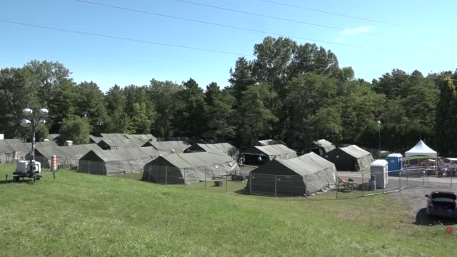 soldiers busily assemble tents with wooden floors lighting and heating in canada's quebec province near the us border to temporarily house a surge in... - québec provincia video stock e b–roll