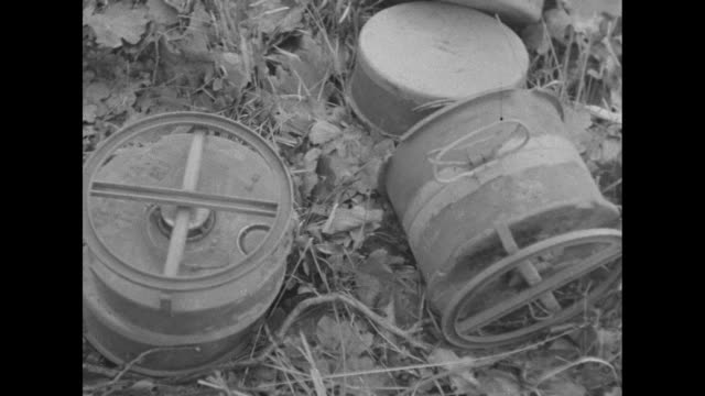VS US soldiers carry antitank mines set them on the ground for placement / CU mines / VS soldier with rifle on his back carries shovel begins to dig...