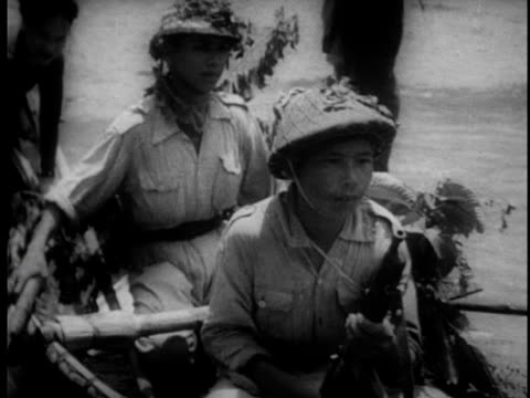 stockvideo's en b-roll-footage met soldiers carry bamboo canoes down to the water and travel down river with supplies / soldiers land on other side and proceed with march - strohoed