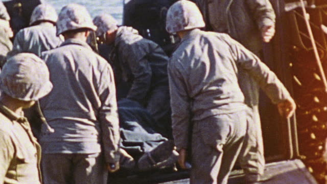 soldiers carry injured comrade on stretchers and place them on to anchored patrol boats ready to take them offshore / iwo jima japan - battle of iwo jima stock videos and b-roll footage