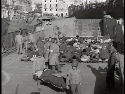 soldiers carry wounded men on stretchers - anno 1944 video stock e b–roll